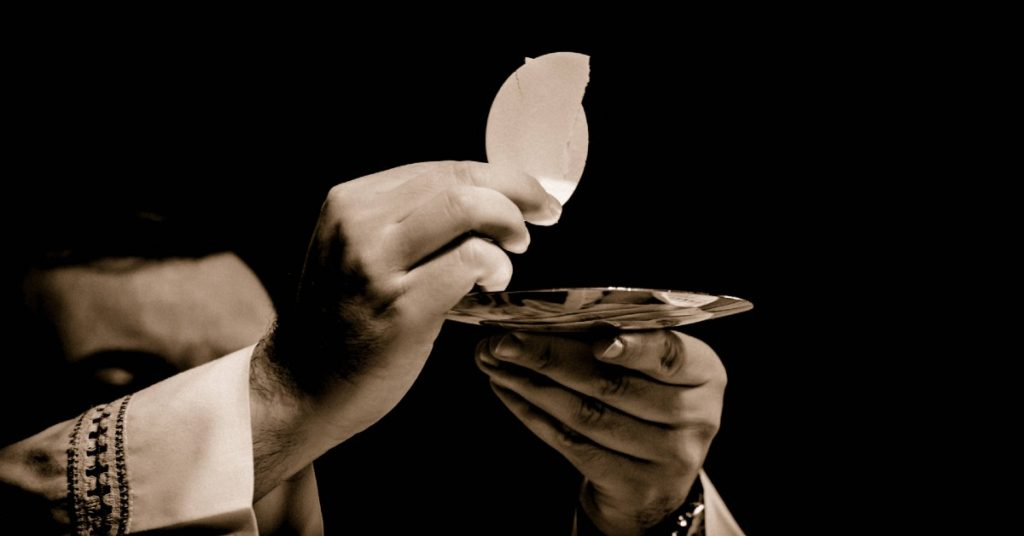 Image of a priest holding up the Eucharist-Body of Christ-over a patent.
