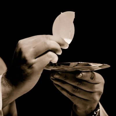 Image of a priest holding up the Eucharist-Body of Christ.
