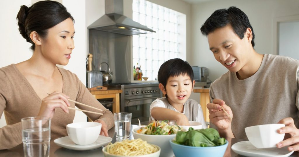 Image of a family-a Mom, young son, and Father-eating dinner together.