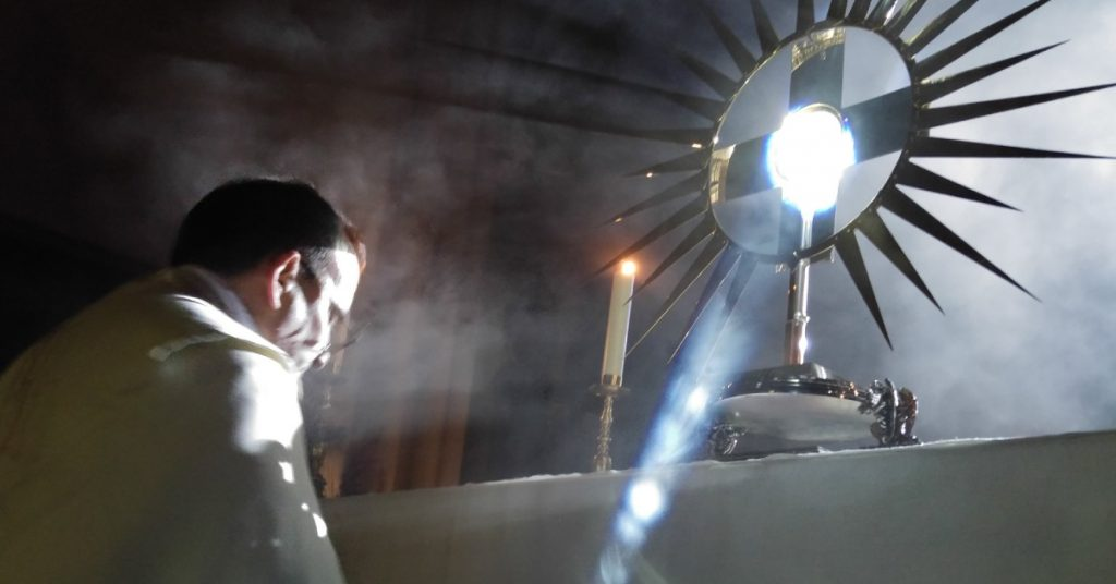 Image of a priest kneeling before the Blessed Sacrament in a monstrance on an altar which is in front of a window where the light is streaming in on the priest and in a ray of light beside him.