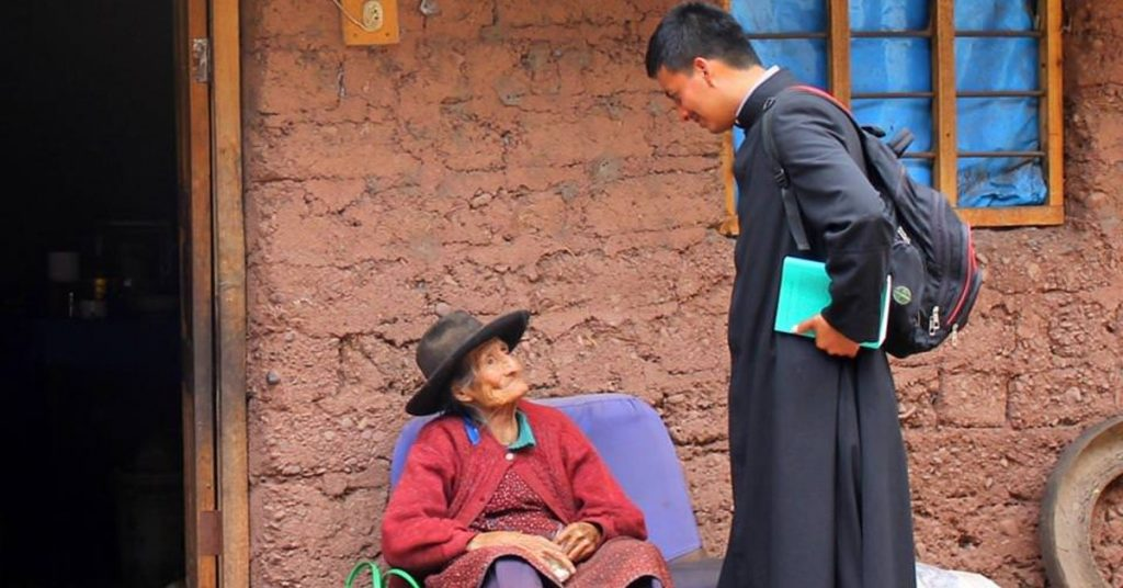 Image of a priest in his black habit wearing a backpack and holding a book under his arm, standing in front of an old woman who is sitting on a chair outside in front of an adobe looking brick home.