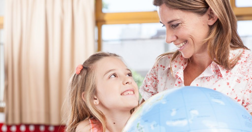 Image of a mom and her daughter smiling at each other and holding a globe of the world between them.