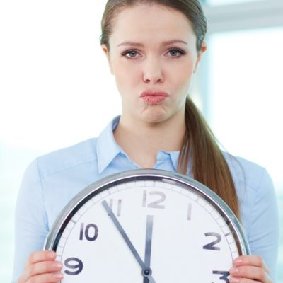 Image of a woman with a frustrated look on her face holding a large circular clock in front of her.