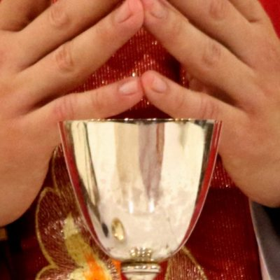 Image of a priest in red vestments with his hands together and fingers touching standing at the altar with a chalice in front of him.