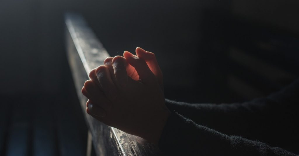 Image of two hands clasped together, resting on the back of a pew in church as light is streaming in from a window on the wall.