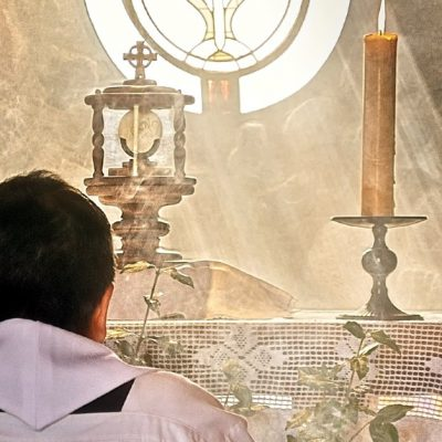 Priest in adoration before the Blessed Sacrament exposed in a monstrance on an altar, flanked by two lit candles. Light is streaming in from a window behind it.