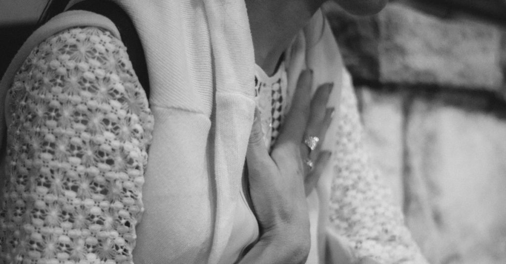 Image of a woman holding a hand to her chest as she prays at church.