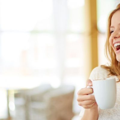 Image of a woman sitting at a table holding a white mug and laughing.