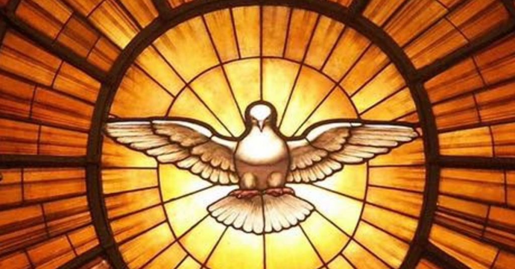 Image of a stained glass window in yellows, gold colors in a circular pattern radiating out from a white dove  in the center that depictss the Holy Spirit.