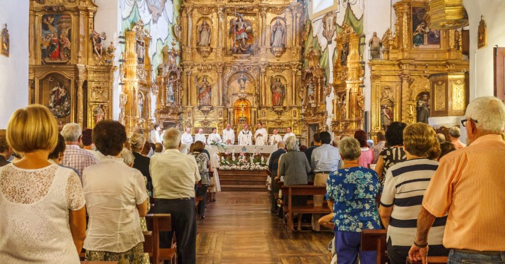 Image of priests behing the altar and people in the pews at a Catholic church during Mass.