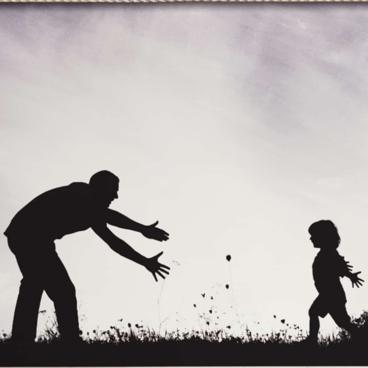 Black and white silhouette image of a father and child facing each other. The Father is bending down with his arms outstretched towards his child.