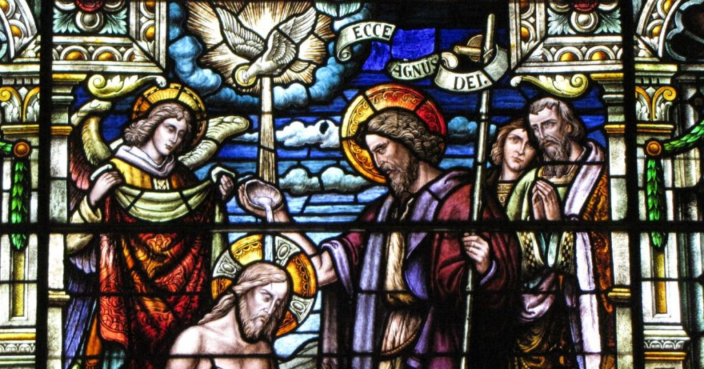 Image of a stained glass window of St. John the Baptist baptizing Jesus in the Jordan. The Holy Spirit is above Jesus and Rays come from Him to Jesus' head. An angel waits behind Jesus and two people stand behind St. John the Baptist looking on.