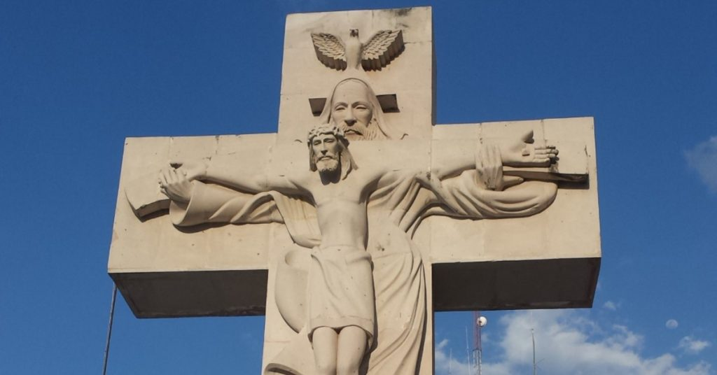 Image of the Trinity on a concrete cross outside: the Holy Spirit as a dove at the top of the cross with God the Father behind Jesus, holding Him up on the cross.