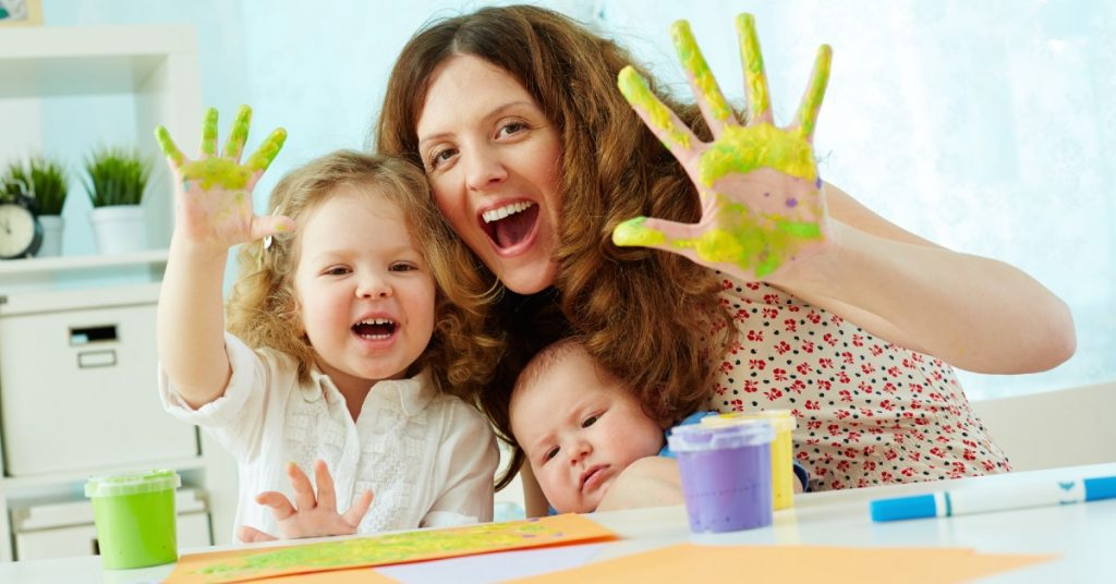 Image of a mom with her little girl and holding a baby whils she and her daughter are smiling at the camera and each are holding up one hand covered in light green paint.