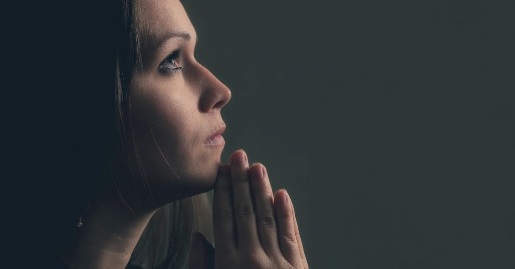 Image of a woman in prayer with her hands folded in front of her chin.