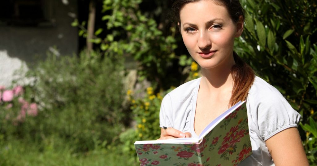 Image of a woman standing outside about to write in a journal and looking at the camera.