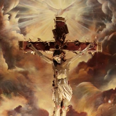 Image of Jesus crucified. He is surrounded by images of clouds and the Holy Spirit as a dove is above the cross.