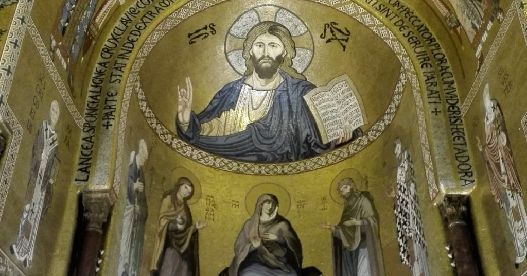 Image of the ceiling inside a Church which picture Jueys holding up one hand while he holds a Bible in the other. There are images of saints on the ceiling also.