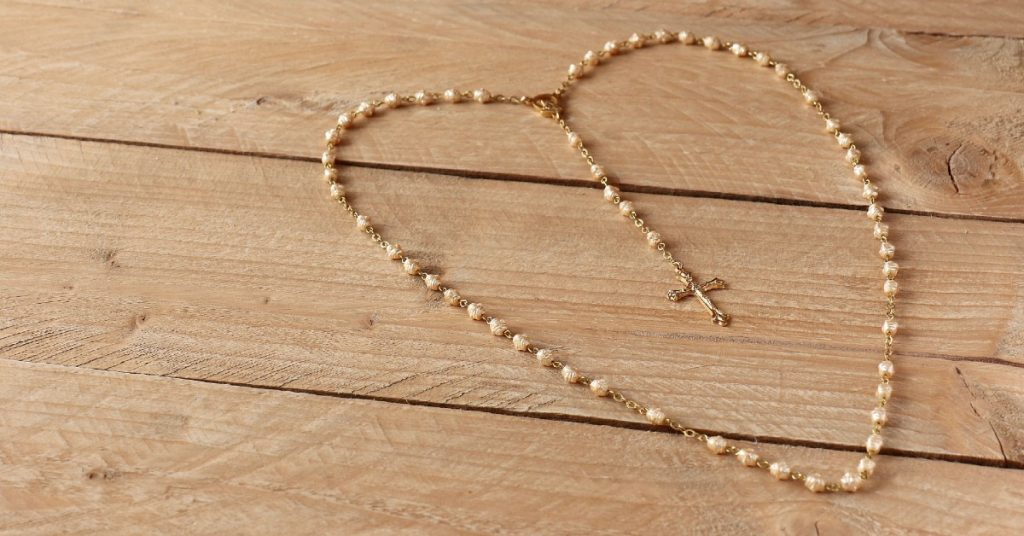 Image of a rosary with pearl like beads shaped into a heart on a wooden surface.