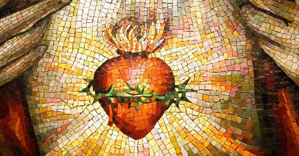Image of a mosaic of the Sacred Heart of Jesus. His hands are on either side of His chest, pulling back His garment so we can gaze upon His heart.