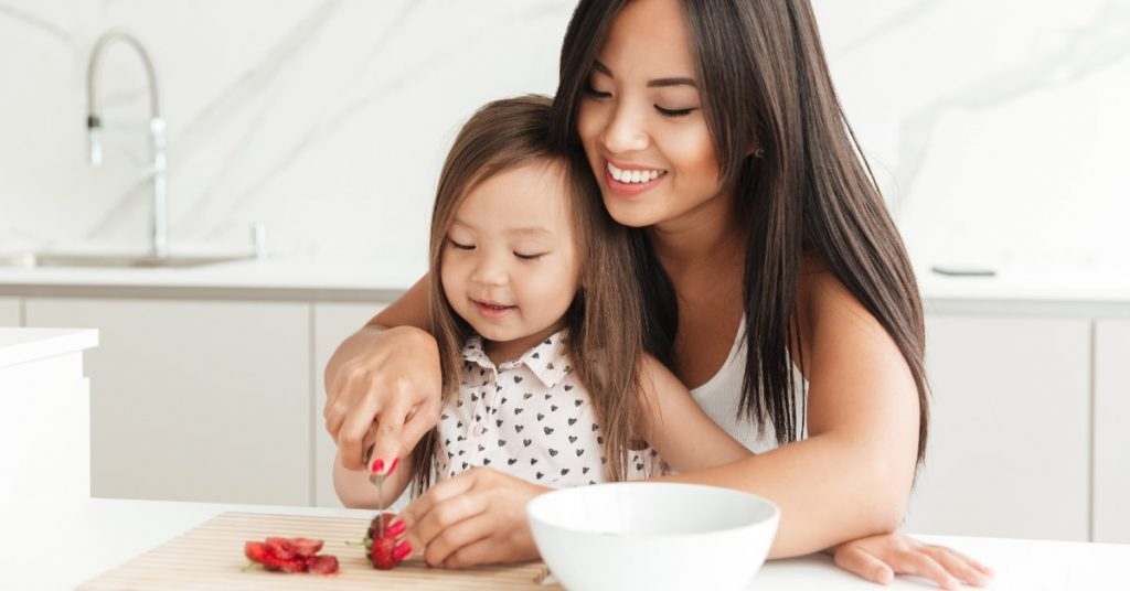 Image of a mom with her young daughter on her lap helping her to cut strawberries.