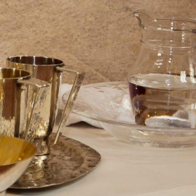 Image of two gold chalices, a small clear pitcher of water, and a bowl for the priest to use for Catholic Mass. While the priest is washing his hands, the faithful can silently pray the Catholic Prayer at the Ablution.