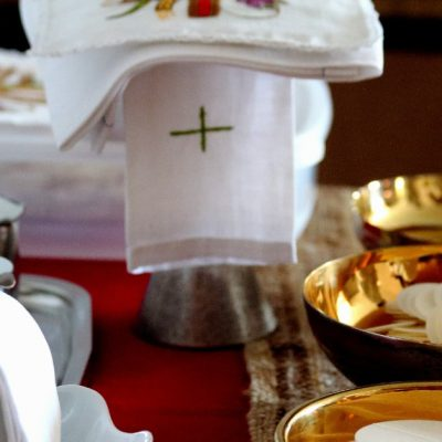 Image of three ciboriums filled with unconsecrated hosts, a covered chalice, and a pitcher in a bowl with a towel covering it.