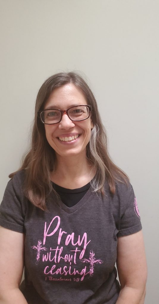 Image of Mary from Blessed Catholic Mom dot com smiling at the camera and wearing a dark grey shirt with pink lettering that reads Pray without ceasing.