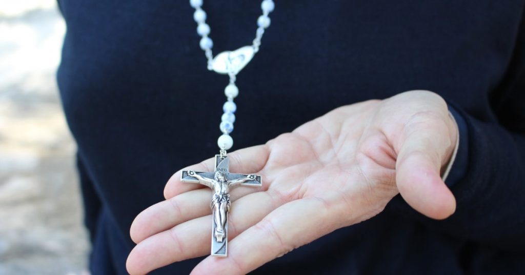 Image of a person,, maybe a priest, wearing black and holding out a Rosary in his hand.