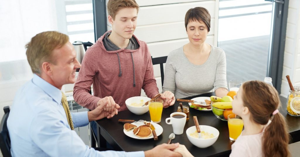 Image of a family of a dad, son, mom, and daughter sitting around a table holding hands as they pray together before eating.