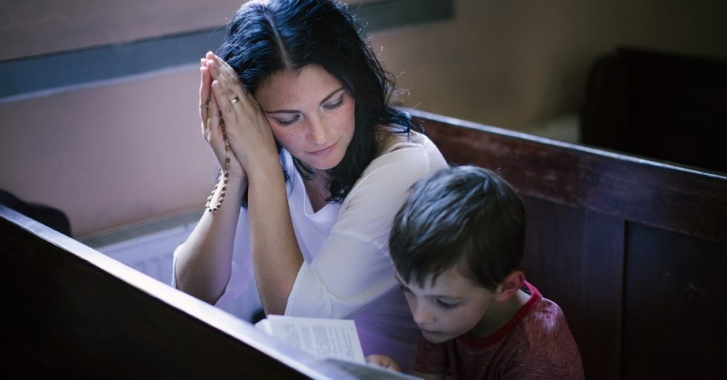 Image of a woman with a Rosary and her son with a prayer book praying together in Church.
