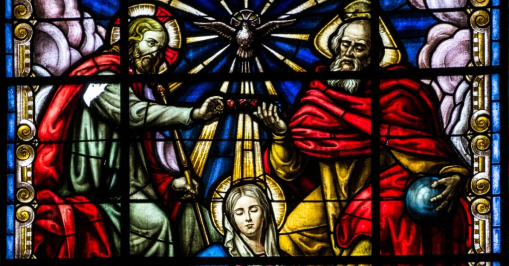 Image of a stained glass window showing the crowing of Mary as Queen of Heaven and earth by Jesus, the Holy Spirit, and God the Father.
