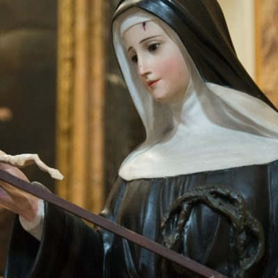 Image of a statue of Saint Rita with a wound from Jesus' crown of thorns on her forehead and holding a crucifix as she lovingly gazes upon it.