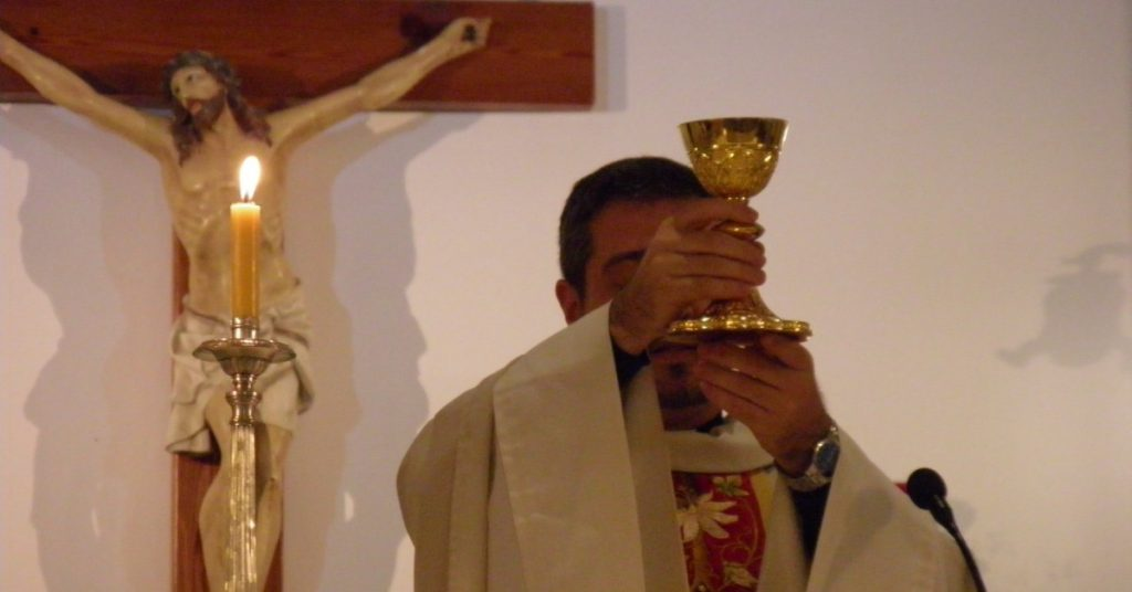 Image of a priest at the altar holding the chalice with the Blood of Christ for the faithful to adore.