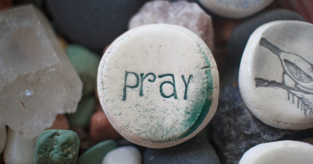 Image of a rocks, and the one in the center has the word pray on it.