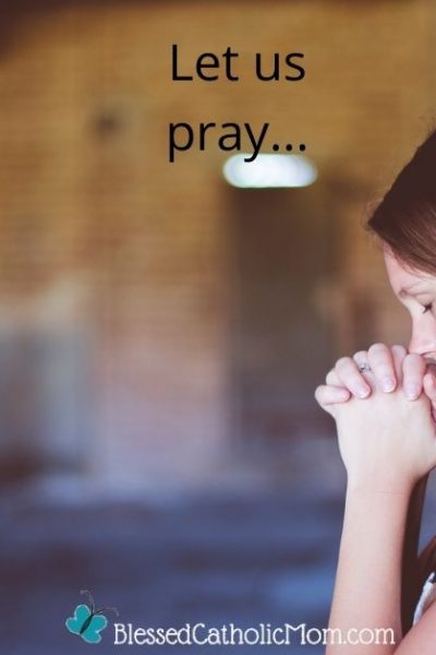 Image of a young woman sitting in a hallway with her back against a brick wall as her hands are folded in prayer, here eyes are closed, and she is resting her face on her hands.