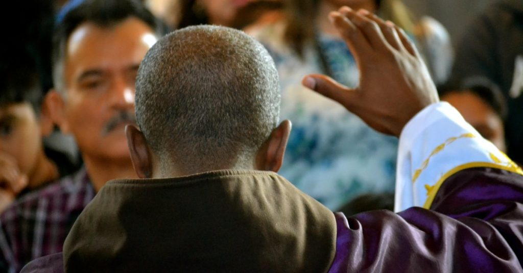 Image of a Catholic priest with his back to the camera raising his hand in blessing in front of the people at Mass.