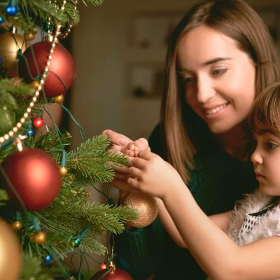 Image of a woman and her daughter decorating a Christmas tree together.