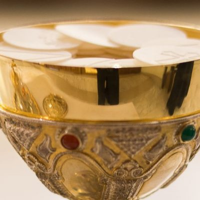 Image of a a gold and jeweled ciborium holding hosts at Mass.