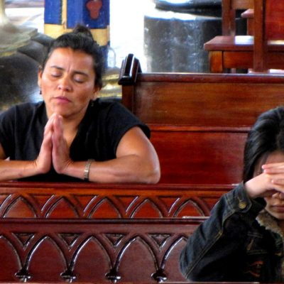 Image of two women kneeling and praying in pews in a church.