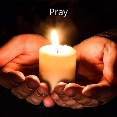 Image of two hands holding a lit candle. The word pray is above the image.