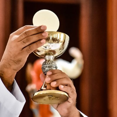 Image of a priest hands holding up the consecrated bread and wine at Mass-the Body and Blood of our Lord Jesus Christ.