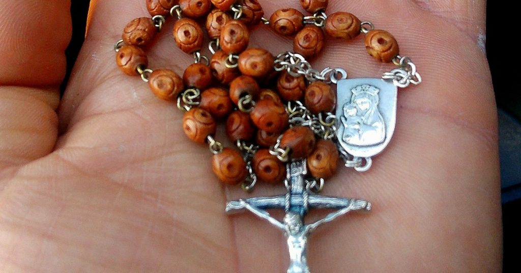 Image of an open hand holding a Rosary.