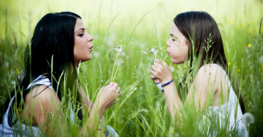 Image of a woman and her daughter sitting in a field facing each other and each of them are blowing a dandelion.