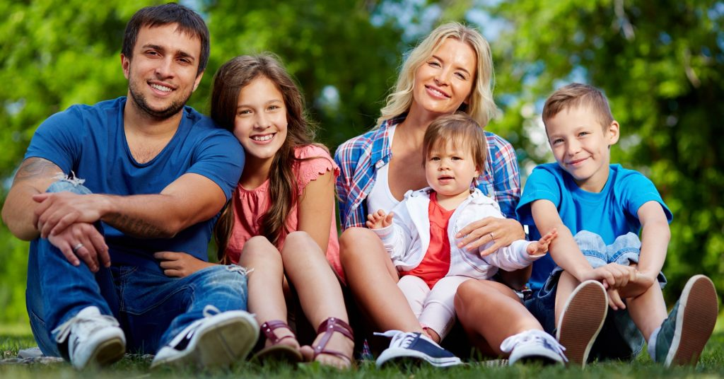 Image of a family of two parents and three kids sitting together on the grass smiling at the camera.
