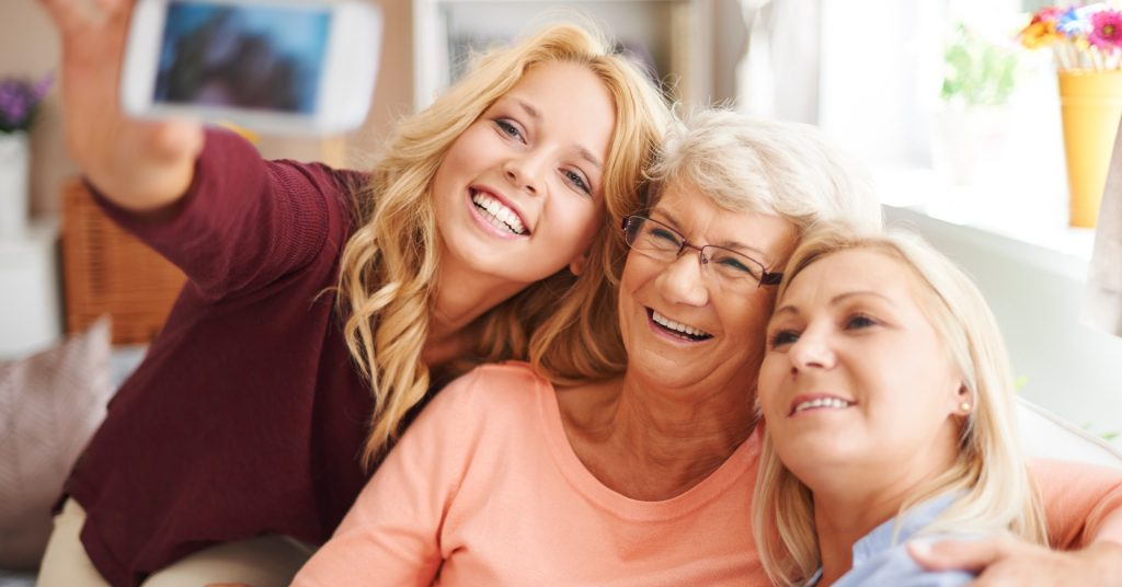 Image of three generations of joyful women sitting on a couch smiling at a camera that one of them is holding up to take a picture.