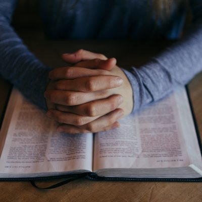 Image of two hands clasped together on to of an open Bible.