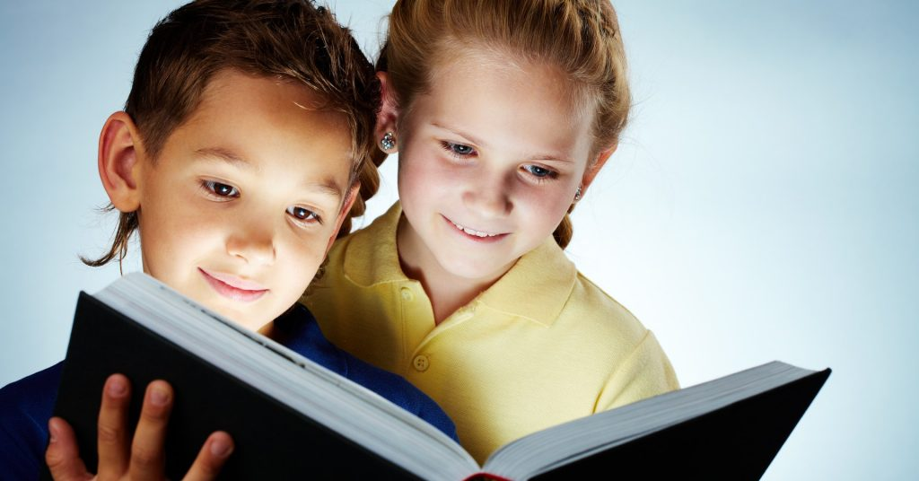 Image of a boy and a girl smiling and looking at an open book.