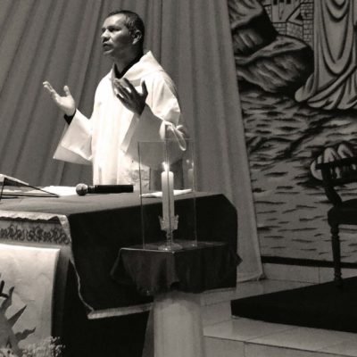 Black and white image of a priest behind the altar at Mass with his hands raised in prayer.