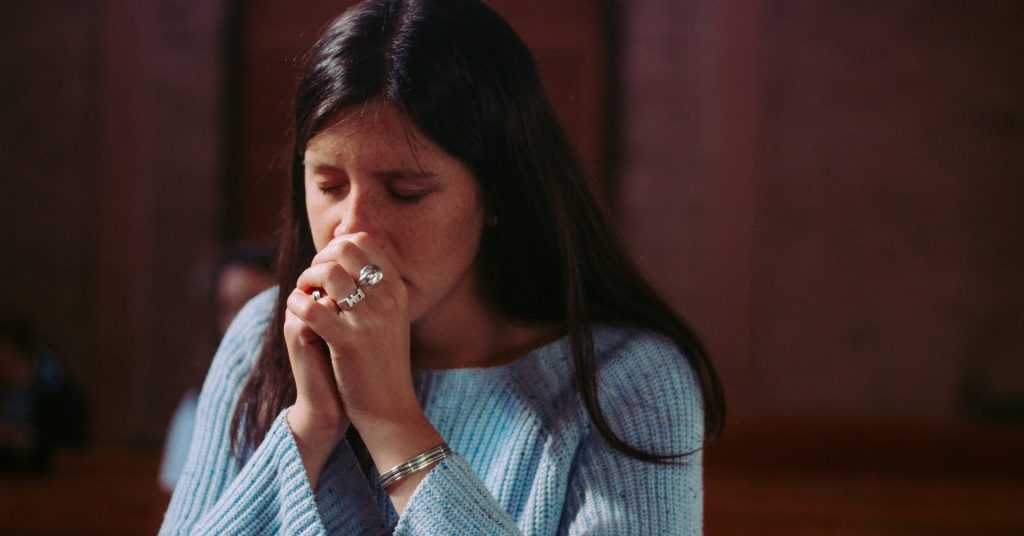 Image of a woman praying with her hands folded in front of her face as she kneels in church.